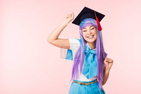 Photo for Anime girl in purple wig and academic cap smiling isolated on pink - Royalty Free Image