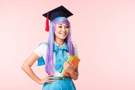 Smiling asian anime girl in academic cap holding books isolated on pink