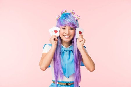 Photo for Happy asian anime girl in purple wig holding cards with hearts isolated on pink - Royalty Free Image