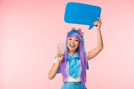 Photo pour Fille asiatique d'anime retenant la bulle de discours et affichant le signe d'idée sur le rose - image libre de droit