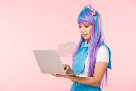 Photo for Beautiful anime girl in purple wig using laptop isolated on pink - Royalty Free Image
