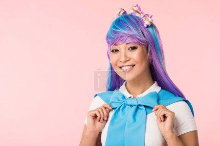 Foto de Smiling otaku girl in purple wig looking at camera isolated on pink - Imagen libre de derechos