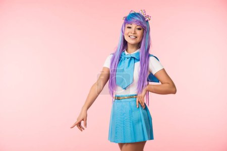 Smiling asian otaku girl in purple wig pointing with finger on pink