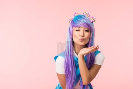 Photo for Asian anime girl sending air kiss and winking isolated on pink - Royalty Free Image