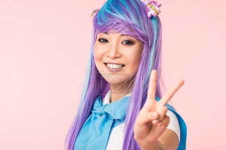 Photo pour Blissful asian anime girl in purple wig showing peace sign isolated on pink - image libre de droit