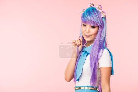 Foto de Hermosa chica de anime asiático en peluca púrpura mirando la cámara aislada en rosa - Imagen libre de derechos
