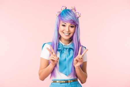 Photo pour Joyful asian anime girl in purple wig showing peace signs isolated on pink - image libre de droit
