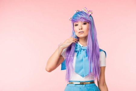 Photo for Pretty asian anime girl in wig looking at camera on pink - Royalty Free Image