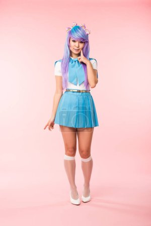 Photo pour Full length view of otaku girl in purple wig smiling on pink - image libre de droit