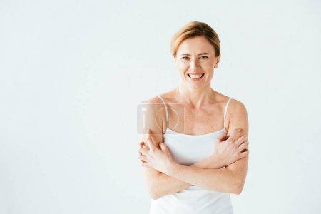 Photo pour Séduisante femme avec une maladie de la peau souriant tout en grattant la peau isolée sur blanc - image libre de droit