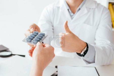 Photo pour Vue recadrée du médecin montrant pouce vers le haut tout en donnant des pilules au patient - image libre de droit