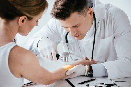 foyer sélectif de dermatologue examinant la main de la femme avec dermatoscope