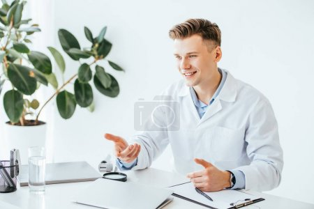 Photo for Handsome and happy doctor in white coat smiling while gesturing in clinic - Royalty Free Image