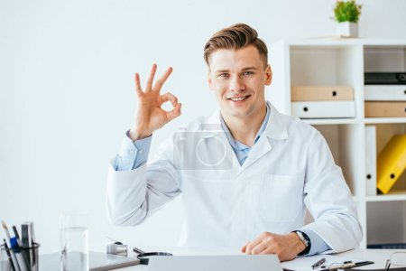 Photo pour Cheerful doctor in white coat showing ok sign in clinic - image libre de droit