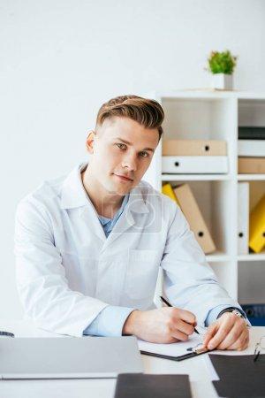 Photo pour Beau médecin en manteau blanc tenant stylo près du presse-papiers - image libre de droit