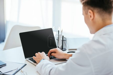 selective focus of doctor using laptop with blank screen