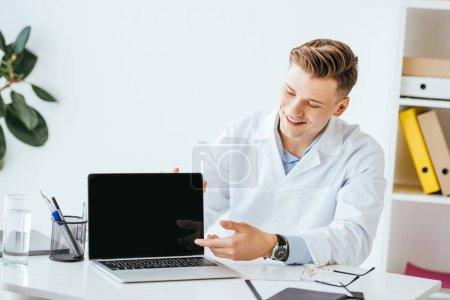 fröhlicher Arzt zeigt mit dem Finger auf Laptop mit leerem Bildschirm