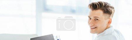 Photo pour Plan panoramique de joyeux et beau médecin regardant la caméra - image libre de droit