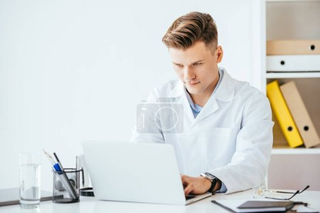 handsome doctor in white coat while using laptop in clinic