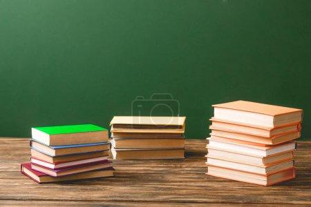 Photo pour Piles de livres sur la surface en bois sur le vert - image libre de droit