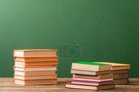 Photo pour Piles de livres colorés sur la surface en bois sur le vert - image libre de droit