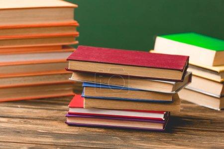 Photo pour Livres à couverture rigide colorés sur la surface en bois isolé sur le vert - image libre de droit