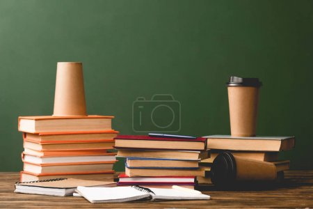 Photo for Books, notebooks and disposable cups on wooden surface on green - Royalty Free Image