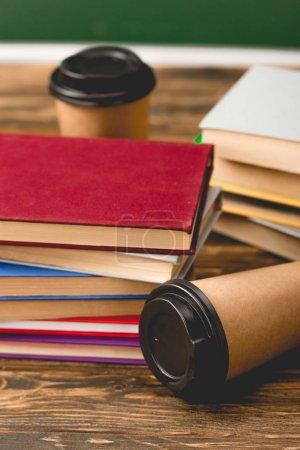 Photo pour Mise au point sélective des livres et des tasses jetables sur la surface en bois sur le vert - image libre de droit