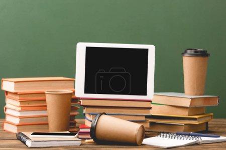 Photo pour Livres, cahiers, tasses jetables, stylos, smartphone et tablette numérique avec écran blanc isolé sur le vert - image libre de droit