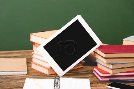Photo pour Livres, cahiers, smartphone et tablette numérique avec écran blanc sur surface en bois isolé sur vert - image libre de droit