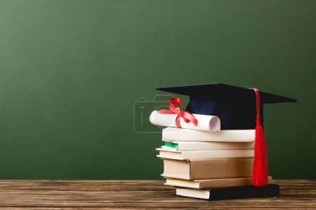 Photo for Books, academic cap and diploma on wooden surface isolated on green - Royalty Free Image