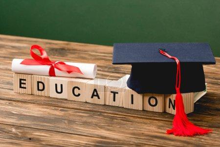 Photo pour Blocs de bois avec lettres, calotte académique et diplôme sur surface en bois isolés sur vert - image libre de droit