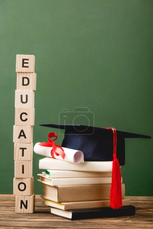 Photo pour Blocs de bois avec lettres, livres, calotte académique et diplôme sur surface en bois isolés sur vert - image libre de droit