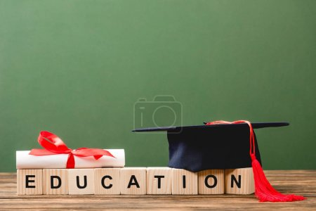 wooden blocks with letters, diploma and academic cap on wooden surface isolated on green
