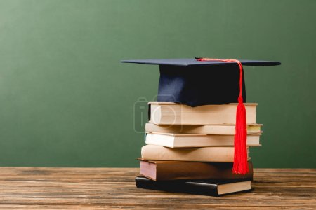 Photo for Books and academic cap on wooden surface isolated on green - Royalty Free Image