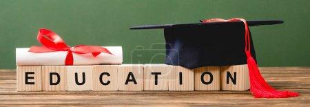 Photo pour Tir panoramique de blocs en bois avec des lettres, diplôme et chapeau académique sur la surface en bois d'isolement sur le vert - image libre de droit
