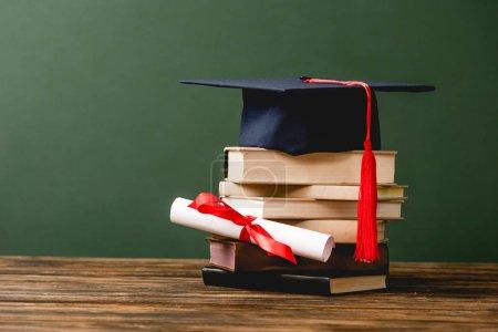 Photo pour Livres, casquette académique et diplôme sur surface en bois isolé sur le vert - image libre de droit