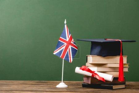 Photo pour Livres, chapeau académique, diplôme et drapeau britannique sur la surface en bois d'isolement sur le vert - image libre de droit