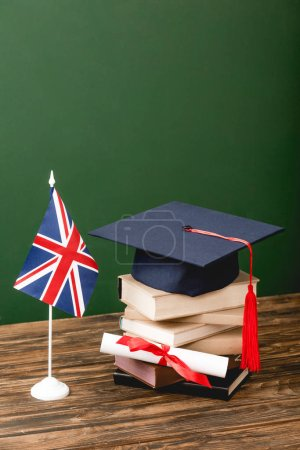 Books, academic cap, diploma and british flag on wooden surface on green