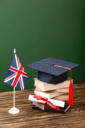 Photo pour Livres, chapeau académique, diplôme et drapeau britannique sur la surface en bois sur le vert - image libre de droit