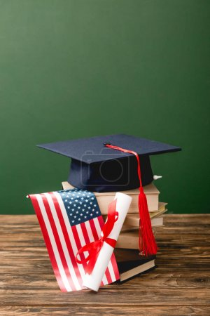 Photo for Books, academic cap, diploma and american flag on wooden surface isolated on green - Royalty Free Image