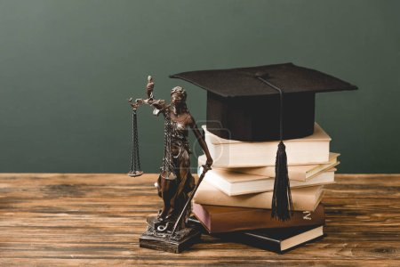 Photo for Themis statuette, books and academic cap on wooden surface isolated on grey - Royalty Free Image