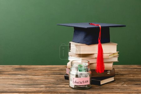 Photo for Books, academic cap and piggy bank on wooden surface isolated on green - Royalty Free Image
