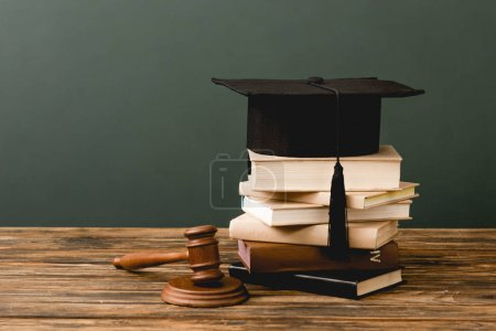 Photo for Stack of books, academic cap and gavel on wooden surface isolated on grey - Royalty Free Image