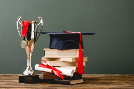 Photo for Books, diploma, academic cap, trophy cup and medal on wooden surface isolated on grey - Royalty Free Image