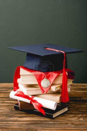 books, academic cap, medal and diploma on wooden surface isolated on grey