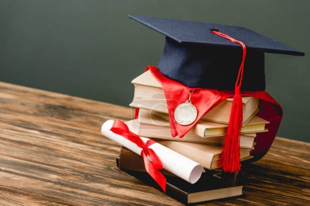 Photo for Books, academic cap, medal and diploma on wooden surface isolated on grey - Royalty Free Image