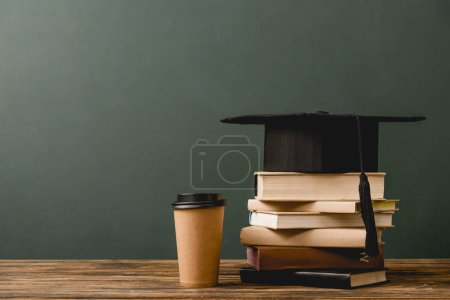 Photo for Books, academic cap and disposable cup on wooden surface isolated on grey - Royalty Free Image