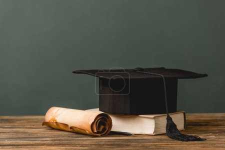 Photo for Book, academic cap and scroll on wooden surface isolated on grey - Royalty Free Image