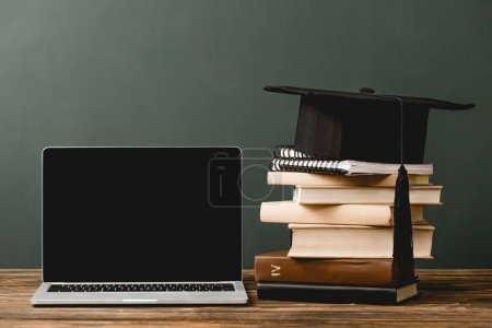 Photo for Books, notebooks, academic cap and laptop with blank screen on wooden surface isolated on grey - Royalty Free Image